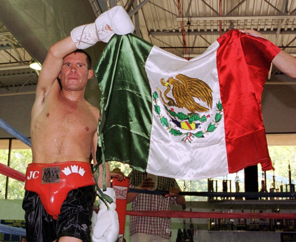 SCOTTSDALE, AR - JULY 24: Mexican boxing legend Julio Cesar Chavez (L) displays his national flag during a workout at a gym 24 July 2000 in Scottsdale, Arizona. Chavez will attempt to regain his WBC superlightweight title when he takes on Russian-born Konstantin Tszyu, who is now based in Australia, on July 29 in Phoenix. (Photo credit should read MIKE FIALA/AFP/Getty Images)